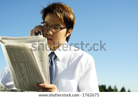 Businessman reading financial newspaper while making a phone call - stock photo