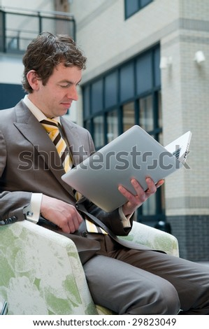 Businessman reading his laptop, special way of using an E-Book. - stock photo