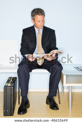 Businessman reading magazine in waiting room