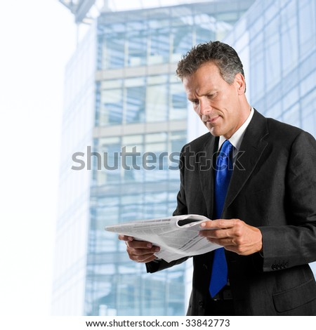 Businessman reading morning news standing against his modern building exterior - stock photo