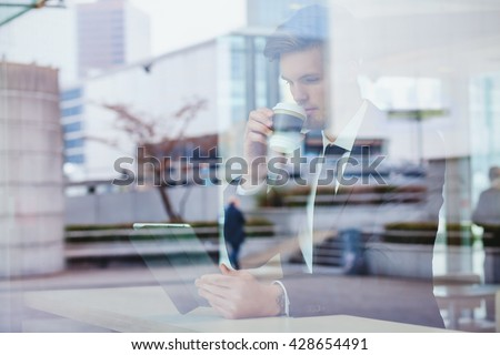 businessman reading news online and drinking coffee in airport cafe - stock photo