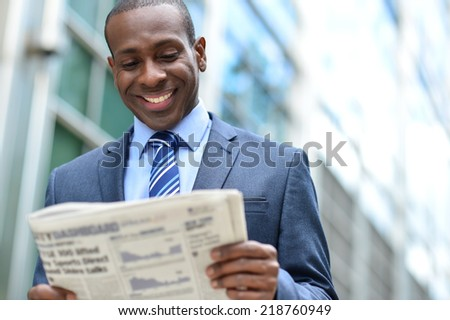 Businessman reading news paper standing outside the office - stock photo