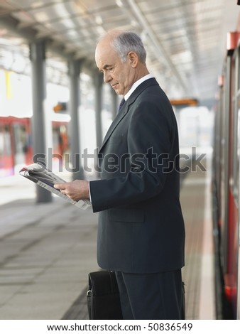 Businessman Reading Newspaper at empty Train Station, side view - stock photo