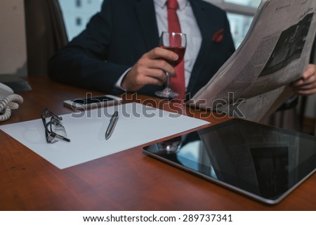 Businessman reading newspaper at his table, selective focus