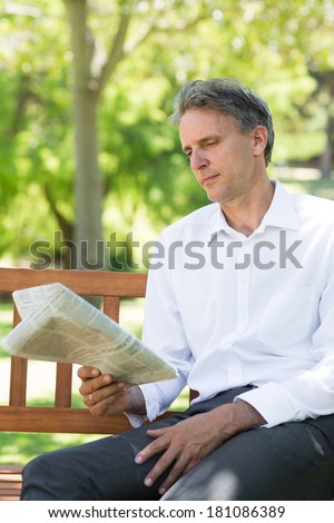 Businessman reading newspaper on bench at the park