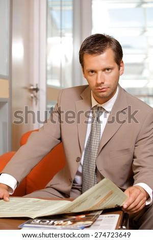 Businessman reading newspaper, portrait - stock photo