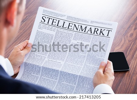 Businessman Reading Newspaper With The Headline Job Market - stock photo