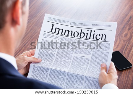 Businessman Reading Newspaper With The Headline Real Estate