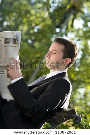 Businessman reading newspapers in park - stock photo