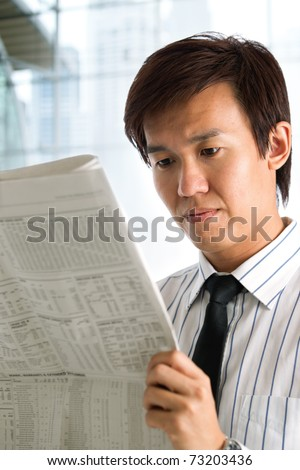Businessman reading the business section of a newspaper. - stock photo