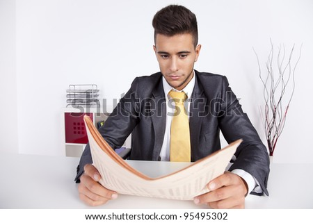 Businessman reading the newspaper in his office - stock photo