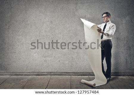businessman reads the paper roll on gray background