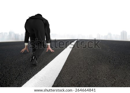 Businessman ready to run on asphalt road with white line and urban scene background - stock photo