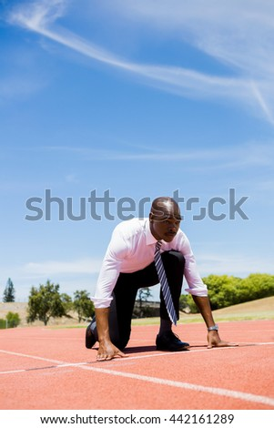 Businessman ready to run on running track