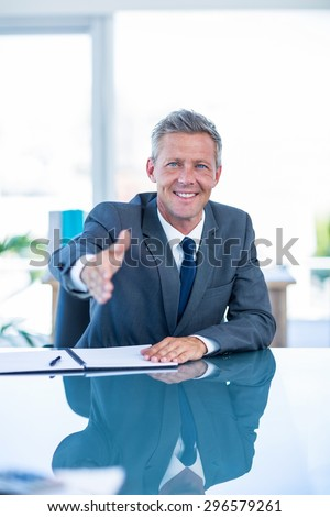 Businessman ready to shake hand in office - stock photo