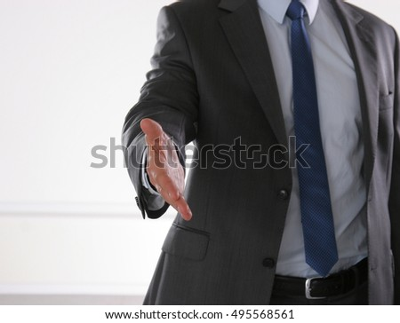 Businessman ready to shake hand in office.