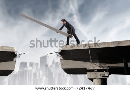 Businessman rebuilding a broken bridge - stock photo