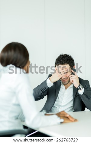 Businessman receiving bad news on the phone and having a headache - stock photo