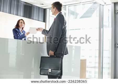 Businessman receiving document from receptionist in office - stock photo