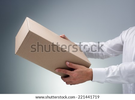 Businessman receiving or giving a cardboard box package or parcel - stock photo