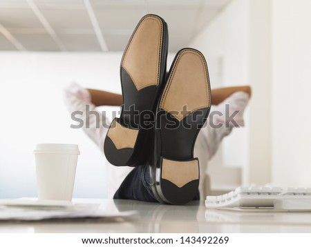 Businessman reclining with his feet up on computer desk in office - stock photo