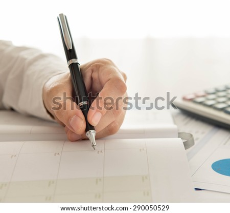 businessman record data on  to schedule a meeting or event - stock photo
