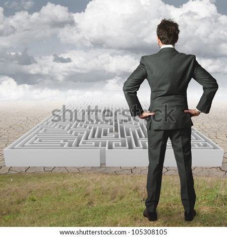 Businessman reflects on solving a maze - stock photo