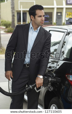 Businessman refueling car tank at fuel station