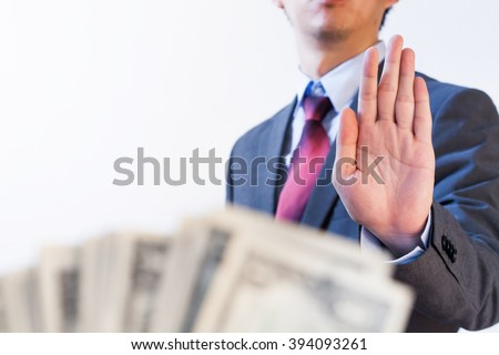 Businessman refuses to receive money - no bribery and corruption concept - stock photo