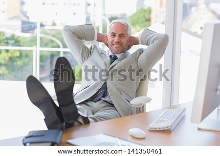 Businessman relaxing at desk and smiling at camera in his office - stock photo