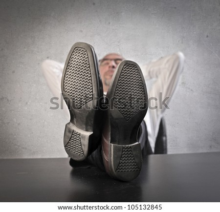 Businessman relaxing at the office with his feet on the table - stock photo