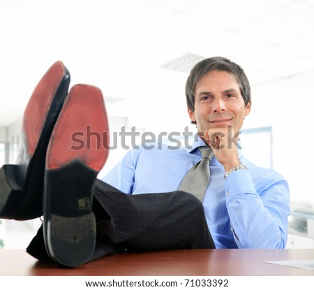 Businessman relaxing at the office with his shoes on the desk - stock photo