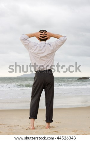 Businessman relaxing barefoot on a beach - stock photo