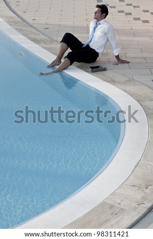 Businessman relaxing by pool - stock photo
