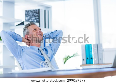 Businessman relaxing in swivel chair in office - stock photo