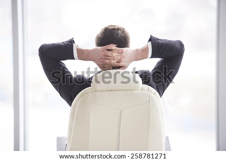 Businessman relaxing in the chair of his office with his hands behind his head.View from the backside. - stock photo