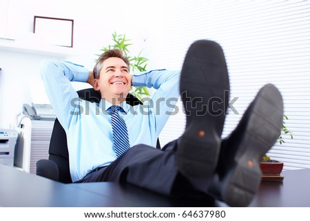 Businessman relaxing in the office - stock photo