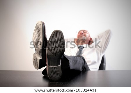 Businessman relaxing on a chair at the office with his feet on the table - stock photo