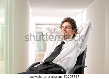 Businessman relaxing on a chair in an office - stock photo