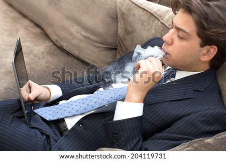 Businessman relaxing on a sofa smoking and working puffing on an electronic cigarette or e-cigarette as he reads his tablet computer