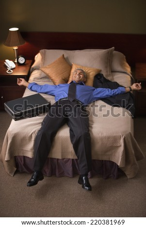 Businessman relaxing on hotel bed - stock photo