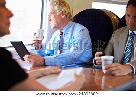 Businessman Relaxing On Train With Cup Of Coffee - stock photo