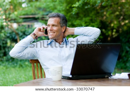 Businessman relaxing outdoor while working with mobile and laptop - stock photo