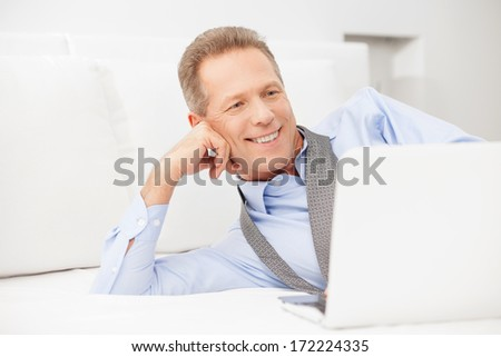 Businessman relaxing. Smiling grey hair man in shirt and tie using laptop while lying on bed   - stock photo