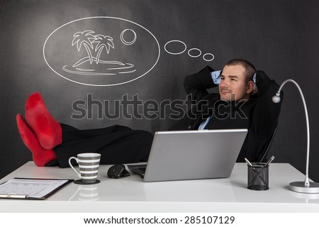 Businessman relaxing with feet over up his desk and dreaming about his vacation - stock photo