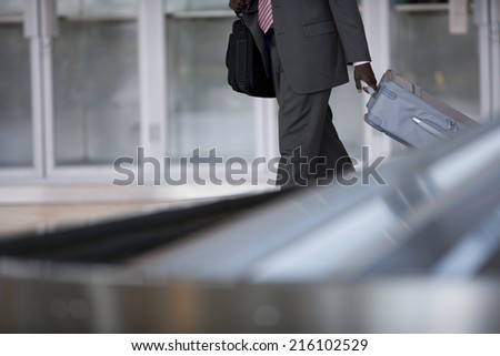 Businessman removing suitcase from luggage carousel in baggage claim - stock photo