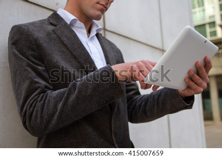 Businessman resting from work and while sending messages and talking with his white tablet. - stock photo