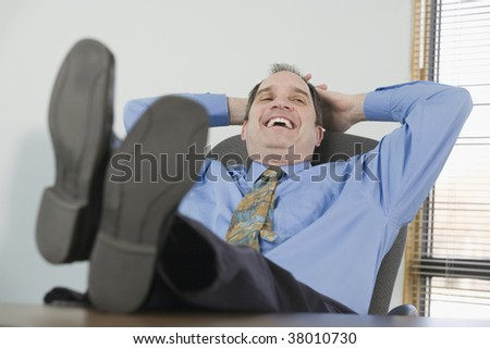 Businessman resting in a chair and smiling - stock photo