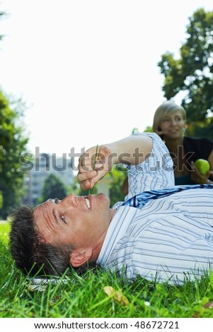 Businessman resting in grass in park, busineswoman talking on mobile in the background. - stock photo