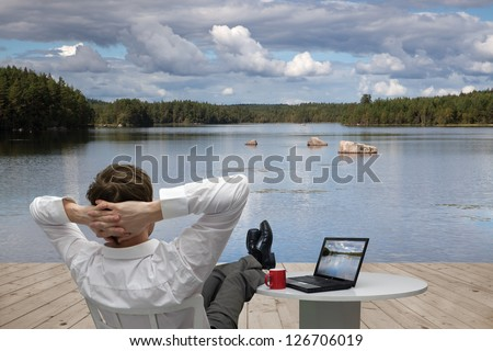 Businessman resting on the shore of lake - stock photo